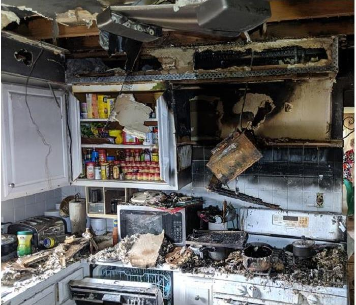 A kitchen with smoke damaged contents and structure.