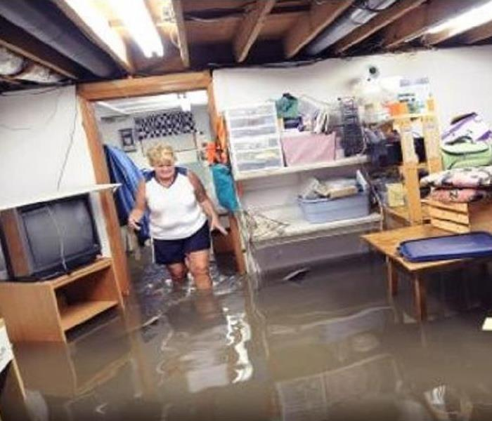 A woman walking through a flooded basement