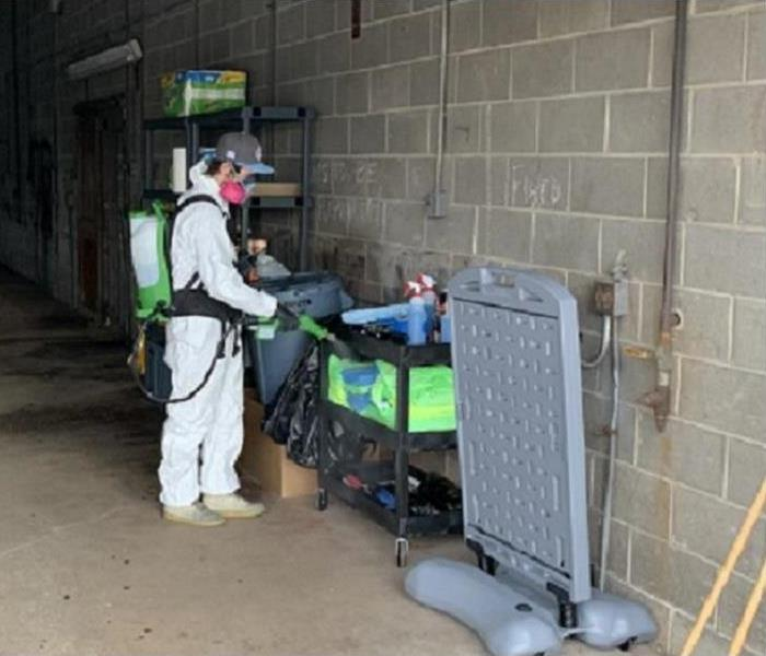 Crew member in a hazmat suit spraying disinfectant in a warehouse