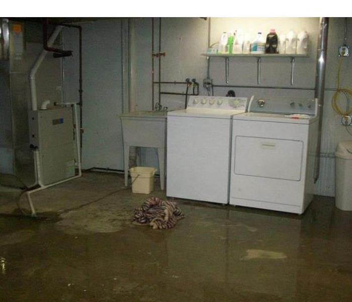 An unfinished basement with standing water on the floor.