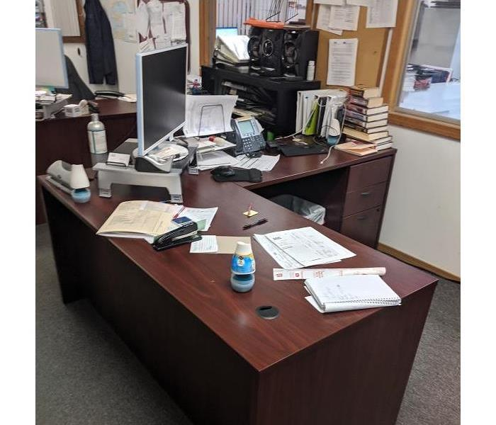An office desk with a computer, phone, stapler, and piles of papers